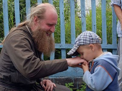 Young boy kissing the hand of an Orthodox priest.