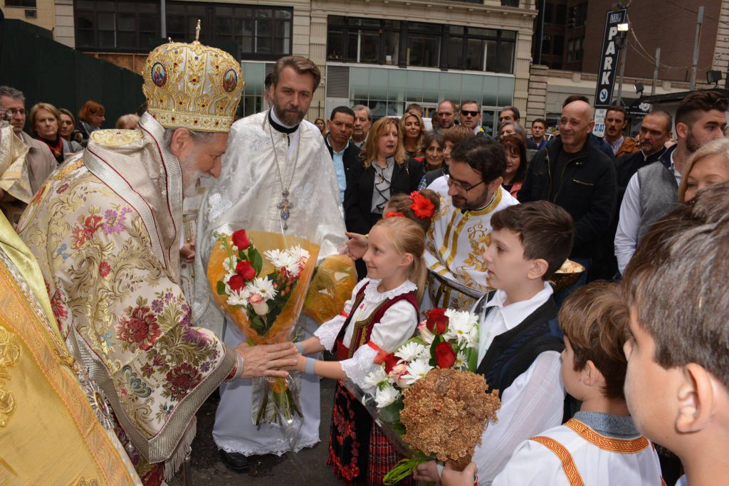 A young child greets His Grace Bishop Irinej of the Serbian Orthodox Church