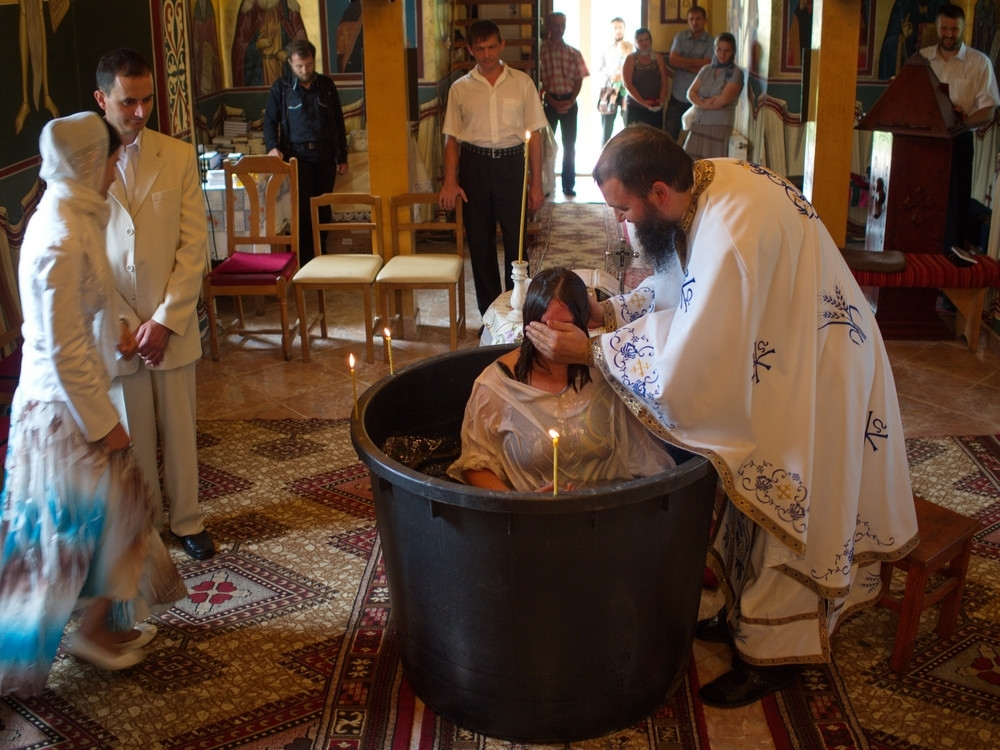 A young woman is born again through holy baptism in an Orthodox church.