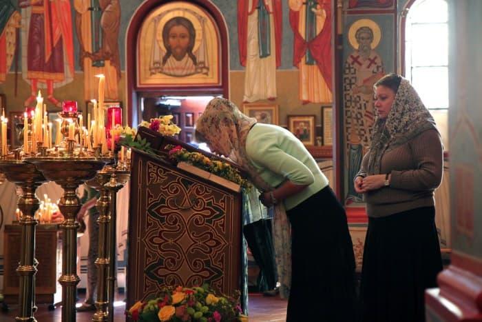 Orthodox women kissing an icon