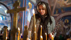 Orthodox woman lighting candles